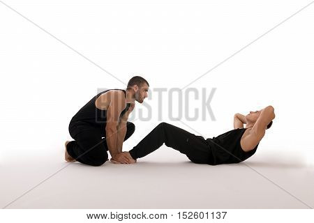 Fitness sport training teamwork and people concept - Man with personal trainer doing sit ups