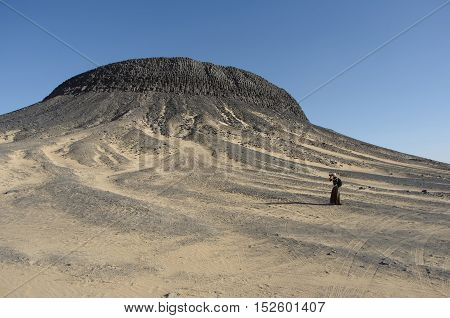Egypt Black Desert, view of the mountain backdrop, photographer girl near the impressive mountain covered with crystals. Black education are of volcanic origin. A popular place for tourists