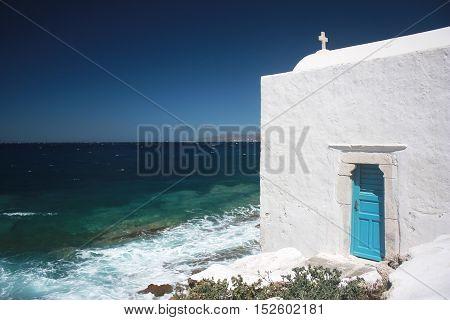 A white Greek ortodox churche in Mykonos with blue sea on the background