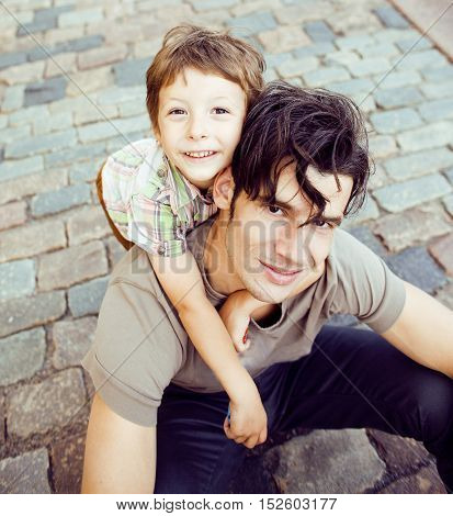 little cute son with modern mature hipster father in city happy smiling hugging, lifestyle people concept close up