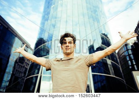 real young man stand in front of modern business building, lifestyle real modern people concept close up