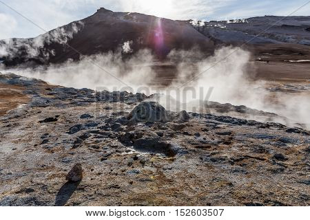 Hot springs and fumaroles produce steam and sulfur vapors on the of Mt. Namafjall in Northeastern Iceland. Backlit to emphasize rising steam, lens flare from sunlight.