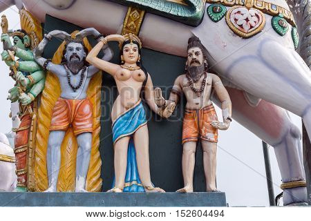Madurai India - October 21 2013: Under the belly of a horse stand a half-naked young woman and two bearded men. All colorful statues at the shrine of Karuppana Sami near Nagamalai village.