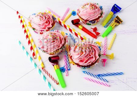 Birthday party concept with decorated pink cupcakes and candles. Homemade cupcakes served for party. Birthday greeting background.