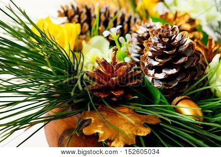 Christmas dinner table decoration with pine branches and golden cones. Christmas centerpiece with golden decor. Christmas party background.