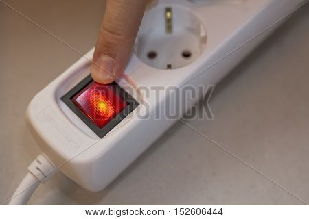 Finger will turn off red button of white socket strip