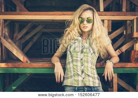Portrait of a Street Style Hipster Girl on Wooden Background. Fashion Woman in Sunglasses Outdoors in Summer. Wooden Background. Toned Cross Processed Photo with Copy Space.