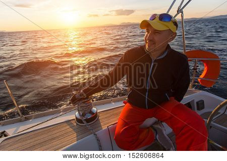 Man sits on a sailboat during sunset.