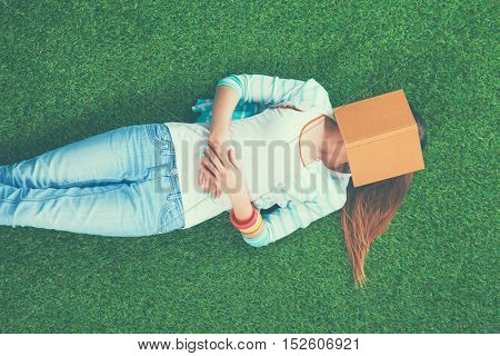 Girl lying on the grass covering the face of the book