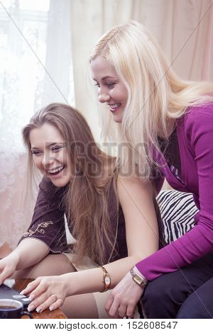 Modern Lifestyle Concept and Ideas. Two Happy Positive and Laughing Caucaisan Girlfriends Having Fun. Working with Laptop Computer Indoors. Vertical Image