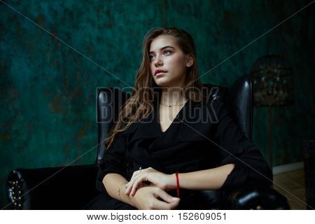 young attractive girl in black trench coat sitting in leather chair in dark classic interior