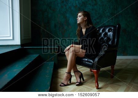 young sexy female in black trench coat sitting in leather chair in dark classic interior