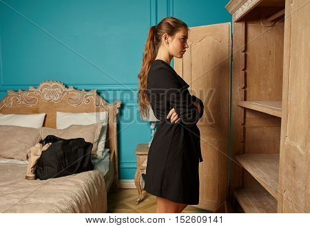 attractive girl with baggage near closet in bedroom of hotel room