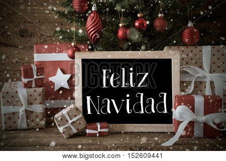 Nostalgic Christmas Card For Seasons Greetings. Christmas Tree With Balls And Snowflakes. Gifts In The Front Of Wooden Background. Chalkboard With Spanish Text Feliz Navidad Means Merry Christmas