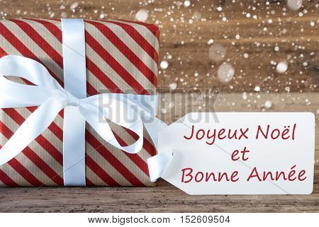 Christmas Gift Or Present On Wooden Background With Snowflakes. Card For Seasons Greetings. White Ribbon With Bow. French Text Joyeux Noel Et Bonne Annee Means Merry Christmas And A Happy New Year