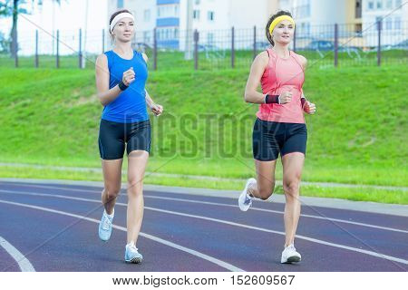 Concepts of Jogging and Healthy Lifestyle. Two Young Caucasian Girlfriends in Athletic Sportswear Having Jogging Exercises Around the Sport Venue. Horizontal Image