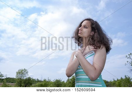 Girl crossed her arms against the sky