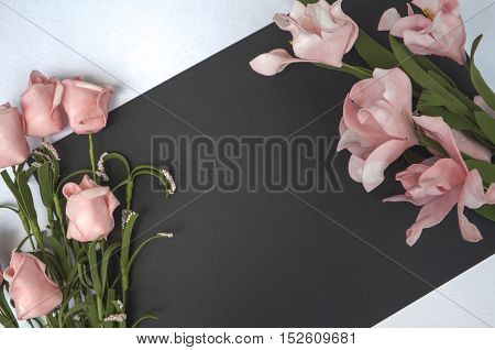 Flat lay composition with blank place and flowers. Romantic photo background for love letters and wedding decor. Table top view with white and black paper. Floral decor mockup
