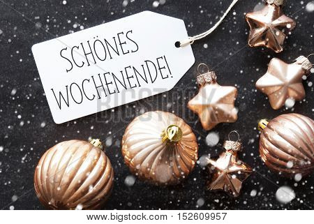 Label With German Text Schoenes Wochenende Means Happy Weekend. Bronze Christmas Tree Balls On Black Paper Background With Snowflakes. Christmas Decoration Or Texture. Flat Lay View