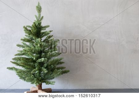 Christmas Card For Seasons Greetings With Christmas Tree. Gray Cement Or Concrete Wall For Urban, Modern Industrial Style. Copy Space For Advertisement
