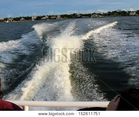 A water taxi makes a wake as it leaves fire island