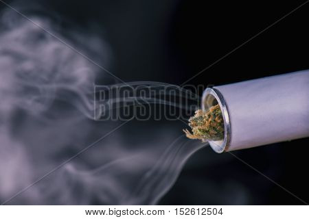 Close up of marijuana joint tip and smoke isolated against black