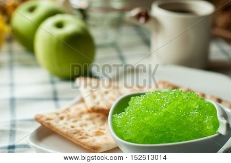 jam apple flavor and crackers, coffee cup on the table, light from the window