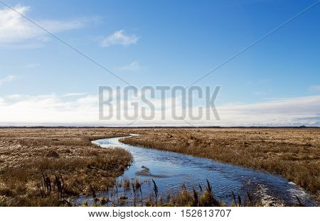 A stream of water winding through a harvested field in a late autumn rural landscape