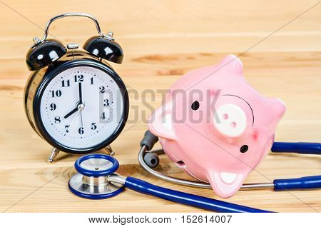 Pink piggy bank with stethoscope and alarm clock on wooden background.