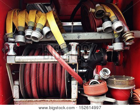 Fire hose and other equipment in a truck, fire water hose connector on board a fire engine, detail of firetruck, firetruck interior with rolled up fire hose