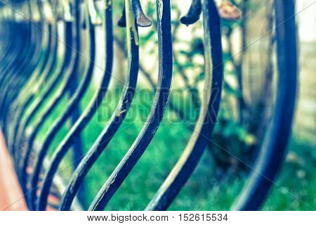 Curved fence blurred with green grass on background