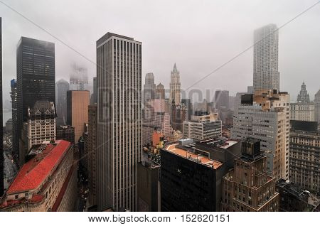 Aerial View of the skyscrapers of downtown Manhattan in New York City in a foggy afternoon.