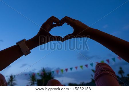 Hands forming a heart shape with sky at dusk