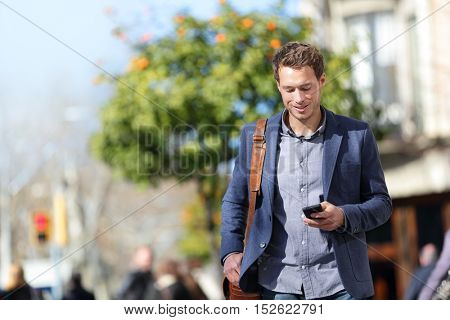 Business man using mobile phone walking to work. Young urban businessman professional on smartphone walking in sunny city street using app playing online game. City lifestyle office commute.