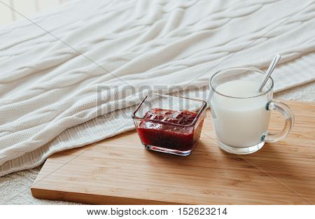 Hot milk in a glass cup and raspberry jam on a wooden board. Treatment of hot drink. Treatment of folk remedies in bed.