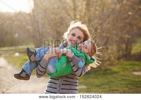 Happy mother and son in the autumn park. Family time. Happiness of childhood and parenthood. Outdoor Activities. Embrace