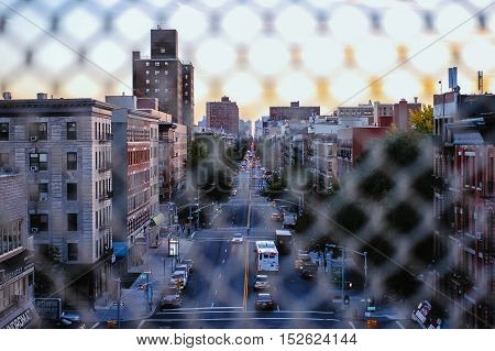 through the fence view of a busy street in upper manhattan