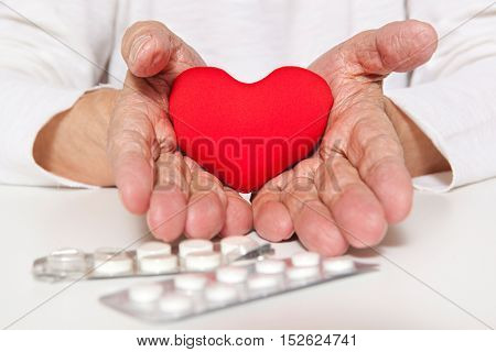 Arterial blood pressure, health and medicine concept - old hands of the elderly giving a red heart
