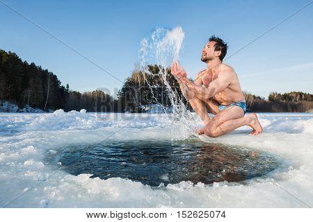 Young man having fun near the ice hole