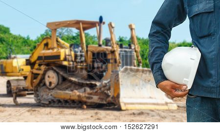 The engineering and safety helmets stood on the details of Closeup skid steer loader excavator at road construction work
