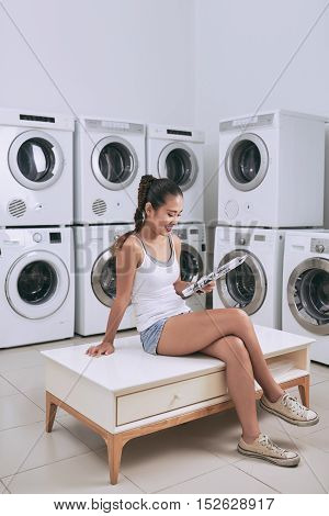 Young woman reading newspaper when waiting in laundromat