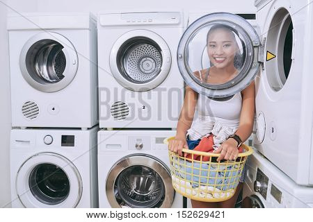Happy woman with basket of fresh laundry standing in laundromat