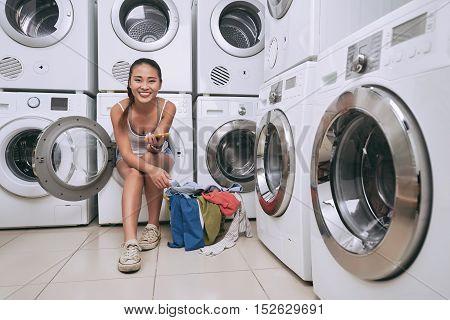 Smiling Vietnamese young woman sitting in washing machine