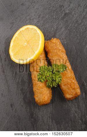 fish finger slice lemon and wet parsley on slate