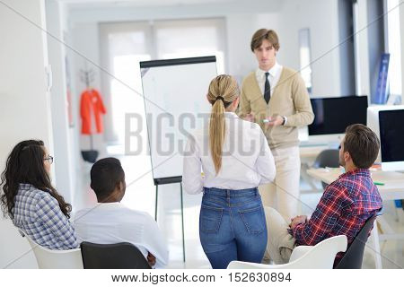 Businessman Giving A Presentation To His Colleagues At Work Standing In Front Of A Flipchart With No