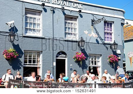 WEYMOUTH, UNITED KINGDOM - JULY 18, 2016 - Tourists relaxing outside The Royal Oak pub in the harbour Weymouth Dorset England UK Western Europe, July18, 2016.