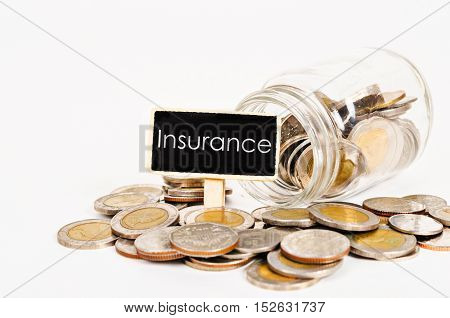 Insurance fund tag with coins in glass jar on white background.