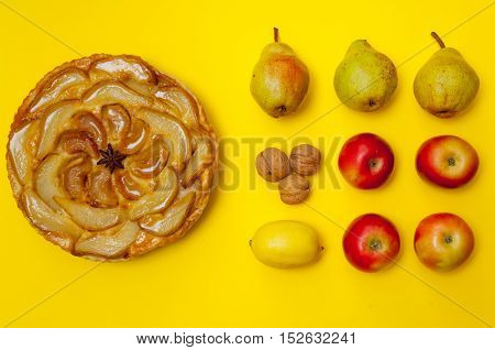 Whole tarte Tatin apple and pear tart pie with fruits on yellow background with copy space