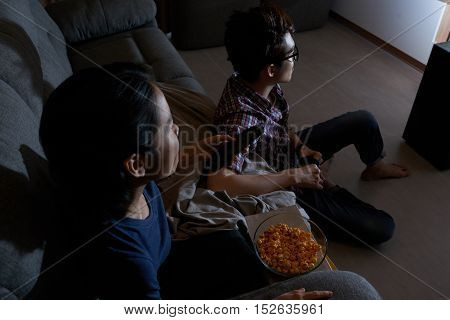 Young people watching popcorn when watching tv at home