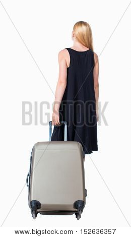back view walking  woman  with suitcase. beautiful girl in motion.  backside view person. Rear view people collection. Isolated over white. Long-haired blonde in black dress pulling a large suitcase